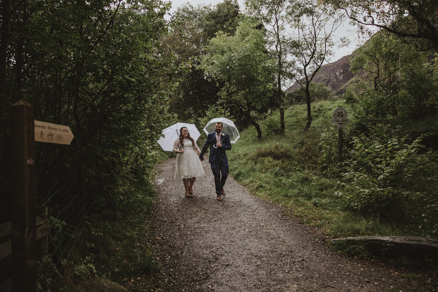 Bride and groom walking in the rain with umbrellas in cumbria