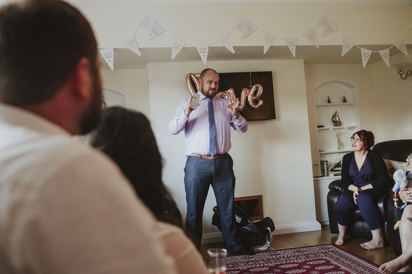 Making a speech with bunting in the background during wedding in cumbria
