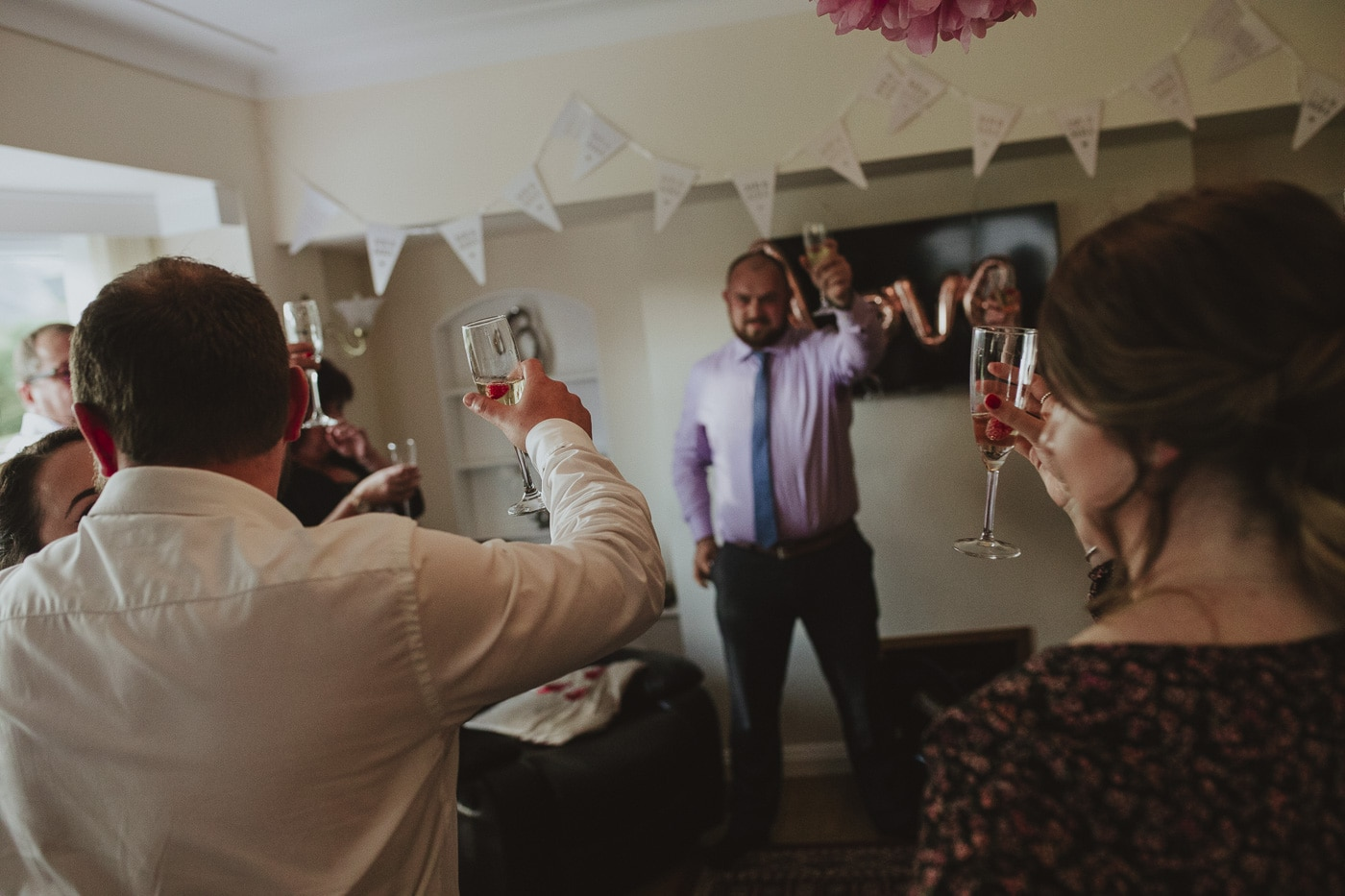 Raising a glass with guests during wedding in cumbria