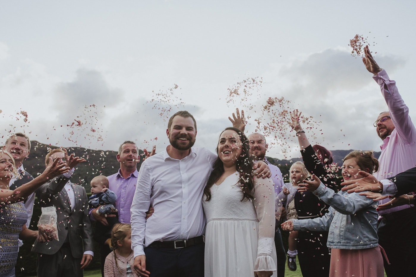 Smiling bride and groom under confetti having wedding photography