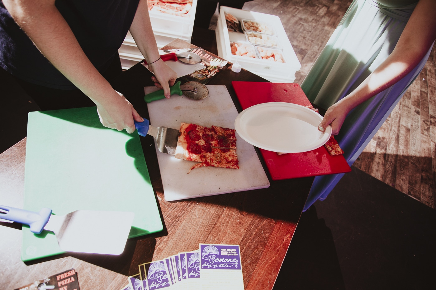Serving pizza at wedding by Joshua Wyborn Photographic