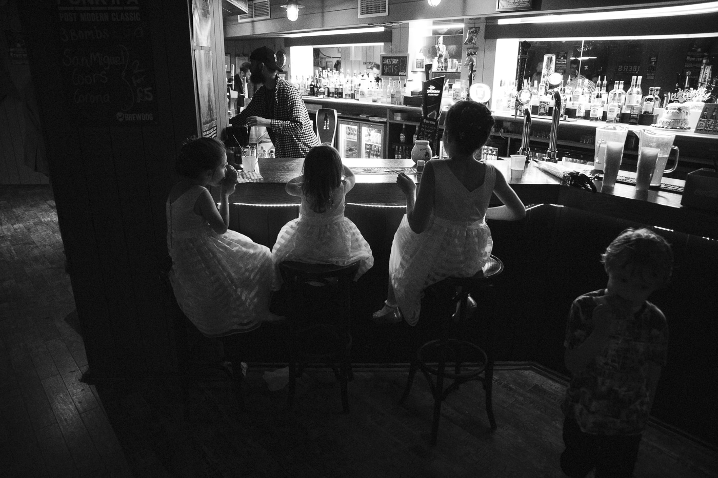 Bridesmaids sitting at bar stools by Joshua Wyborn Photographic