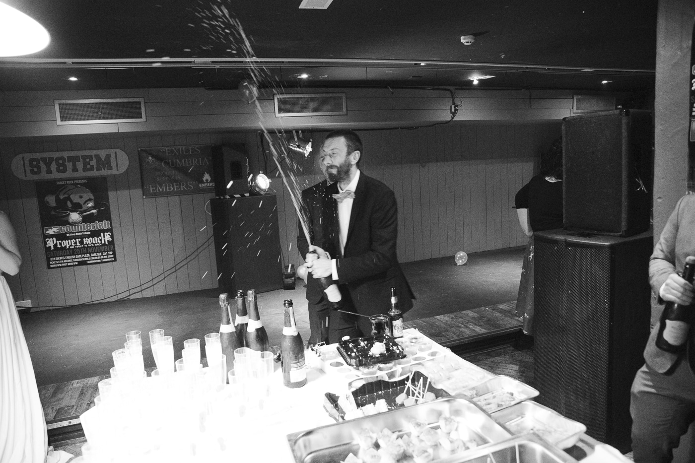 Groom spraying bottle of bubbly by Joshua Wyborn Photographic