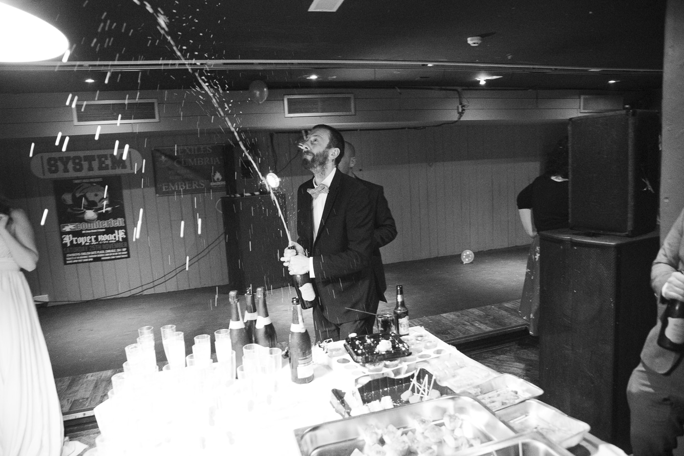 Man spraying bottle of champagne by Joshua Wyborn Photographic