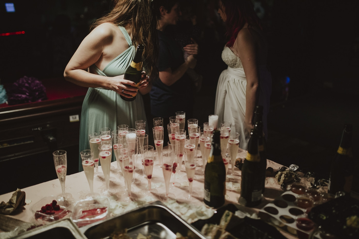 Pouring prosecco with raspberries by Joshua Wyborn Photographic