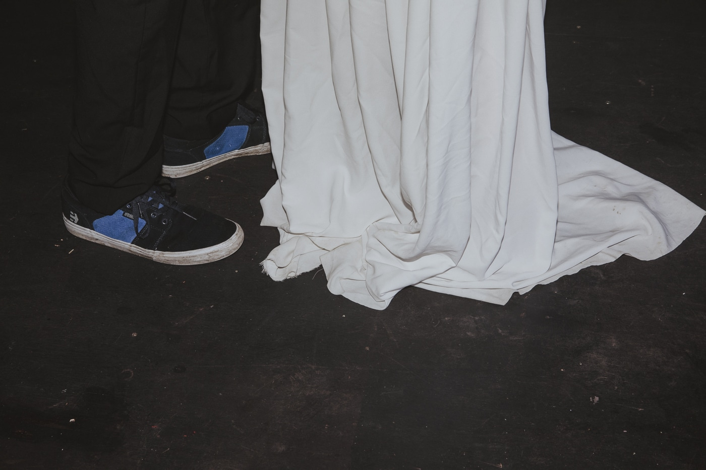 Bride in wedding dress and groom in trainers by Joshua Wyborn Photographic