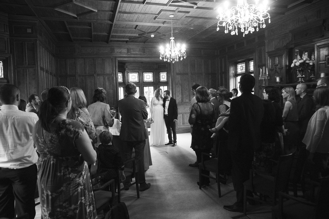 Bride and groom in wood panelled room by Joshua Wyborn