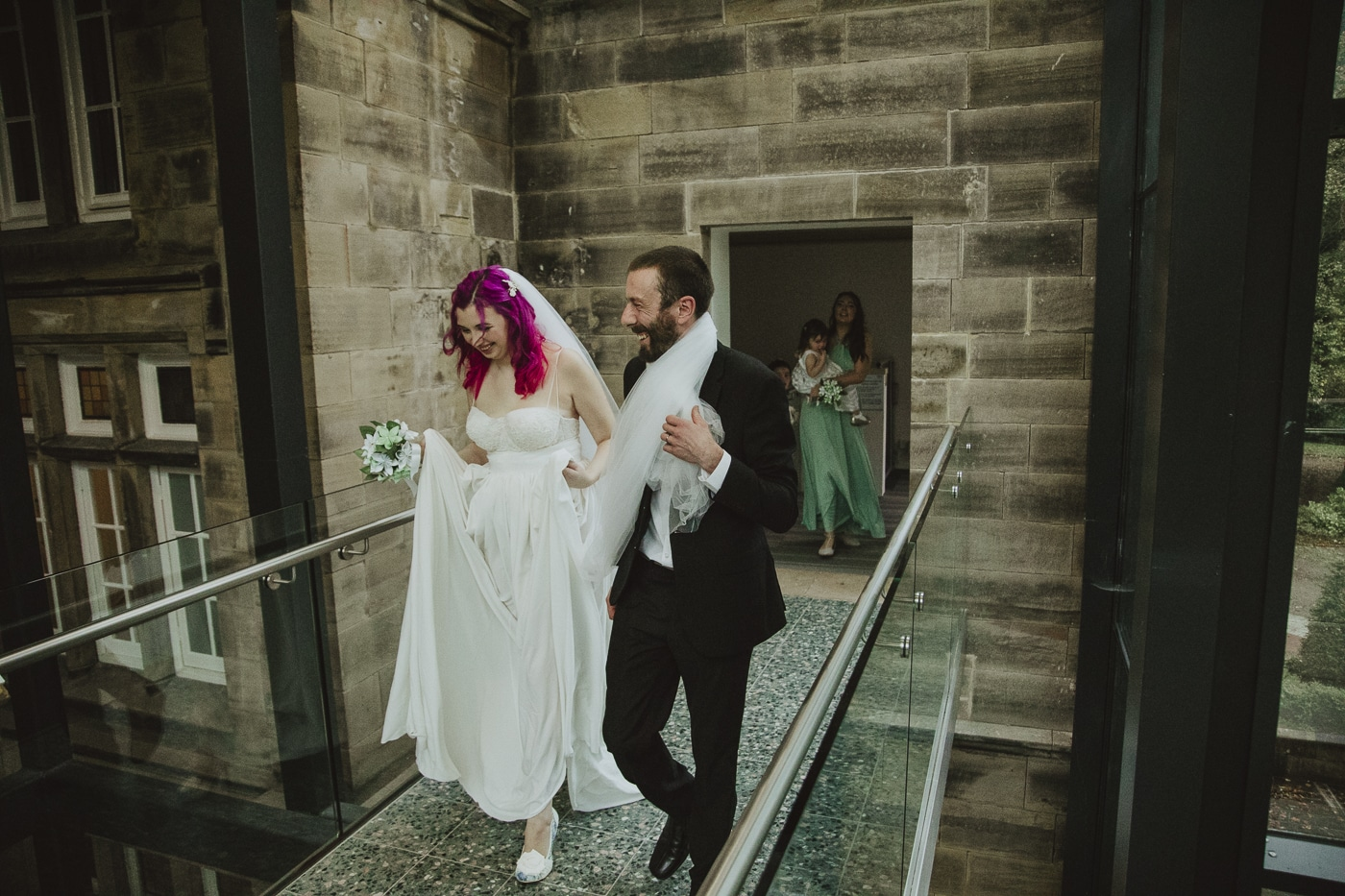 Bride and groom walking across bridge by Joshua Wyborn