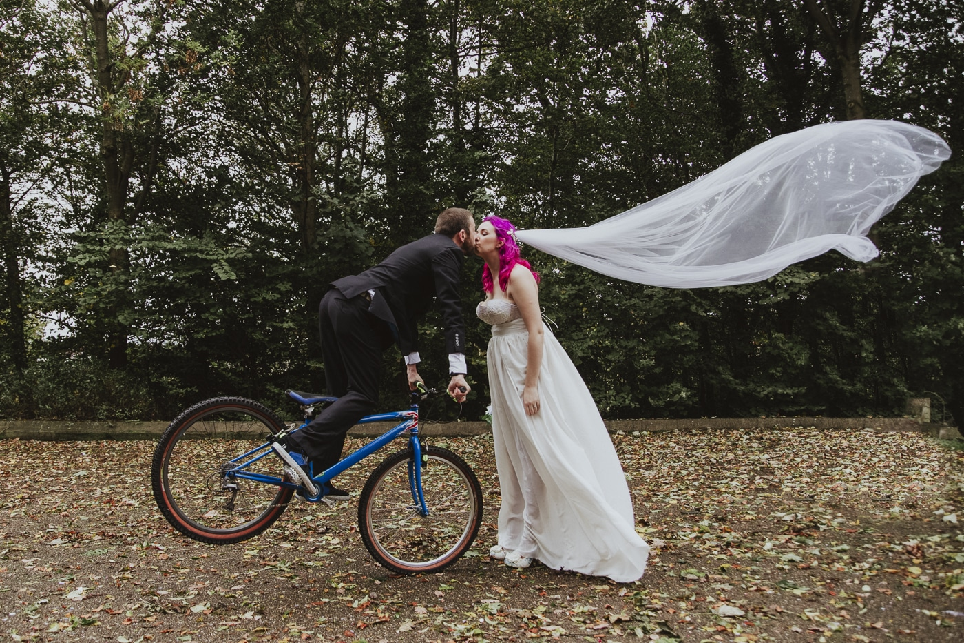 Bride with veil and groom on bike kissing by Joshua Wyborn
