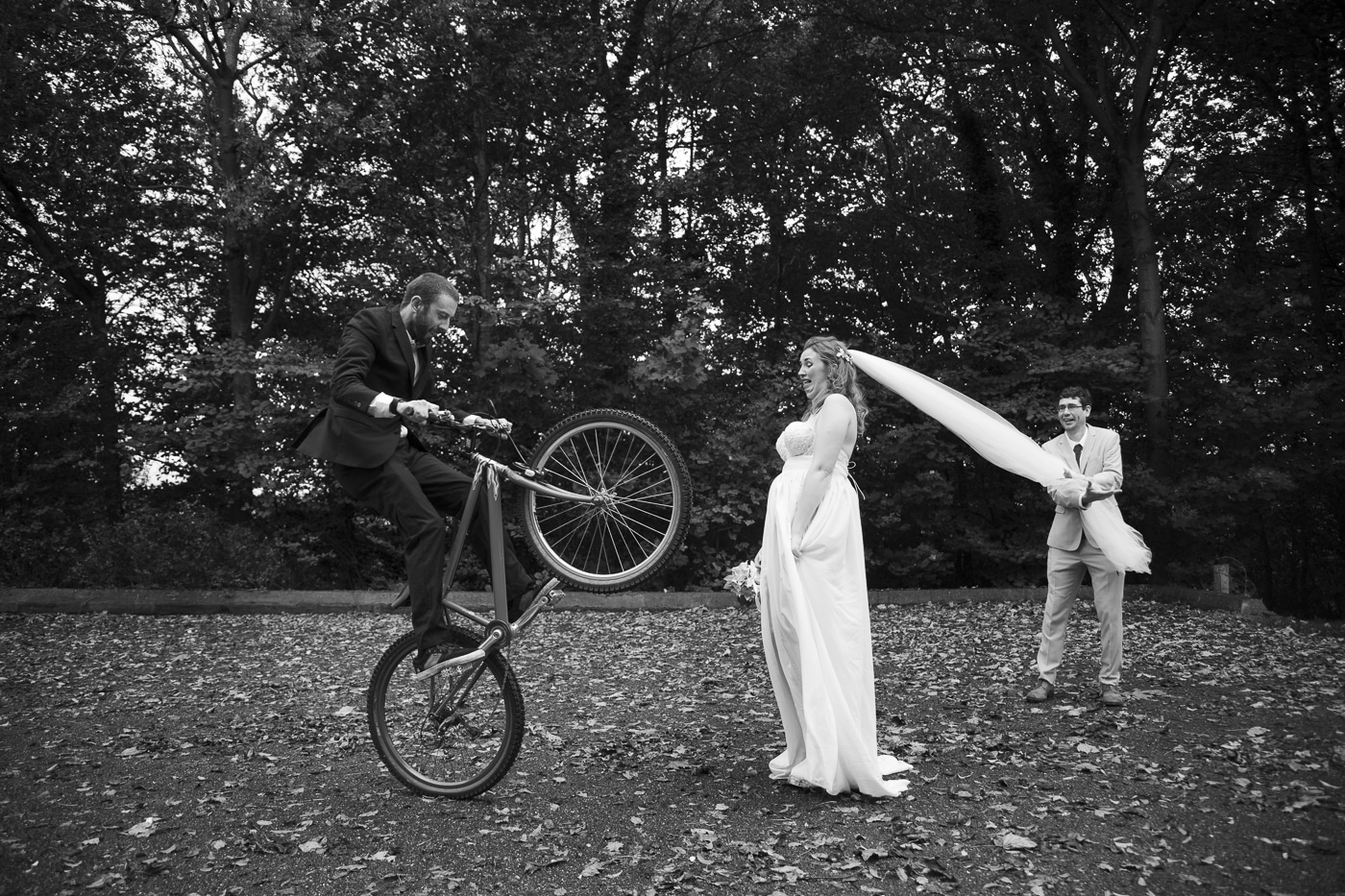 Groom doing tricks on bike and bride with veil by Joshua Wyborn