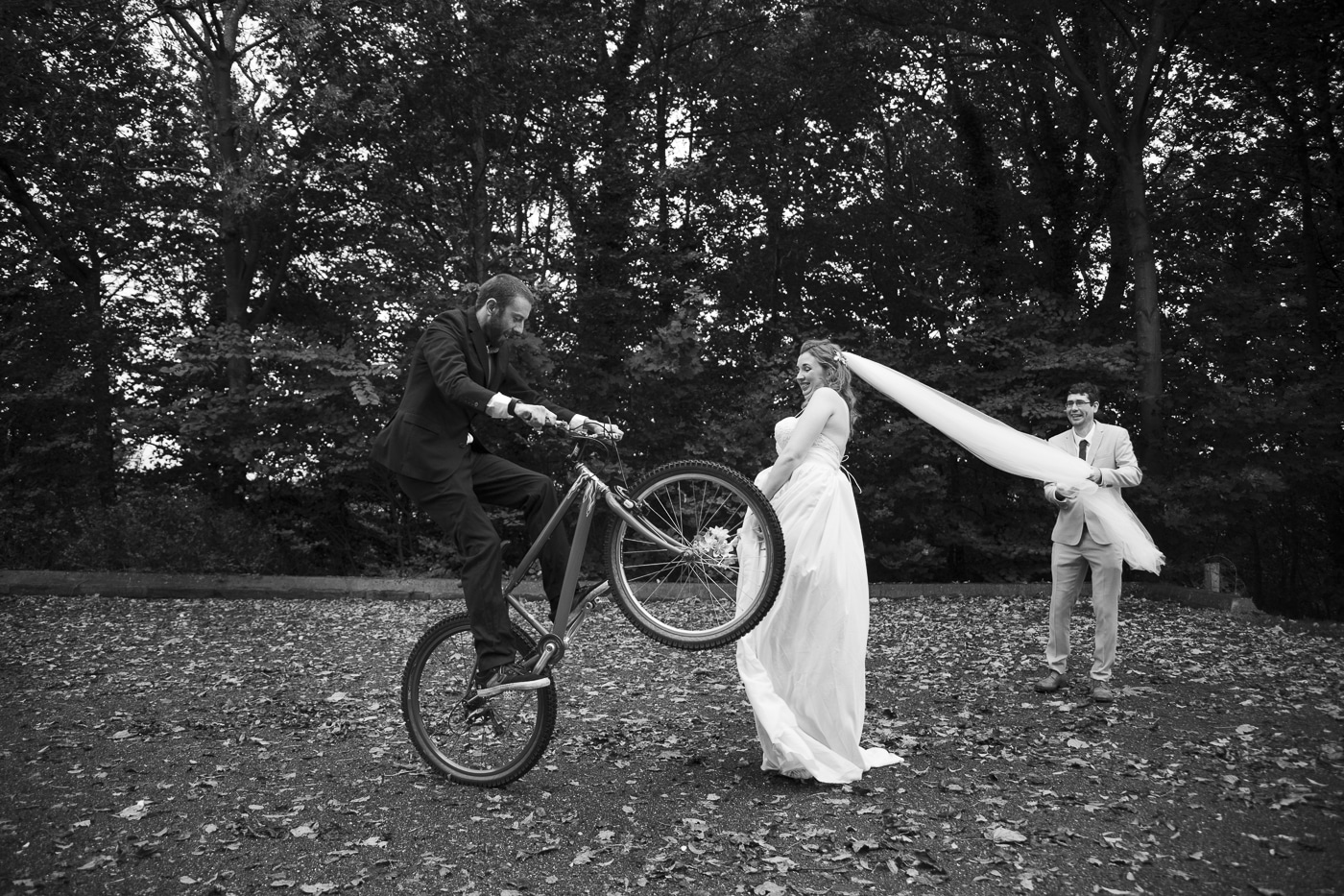 Groom on mountain bike and bride by Joshua Wyborn