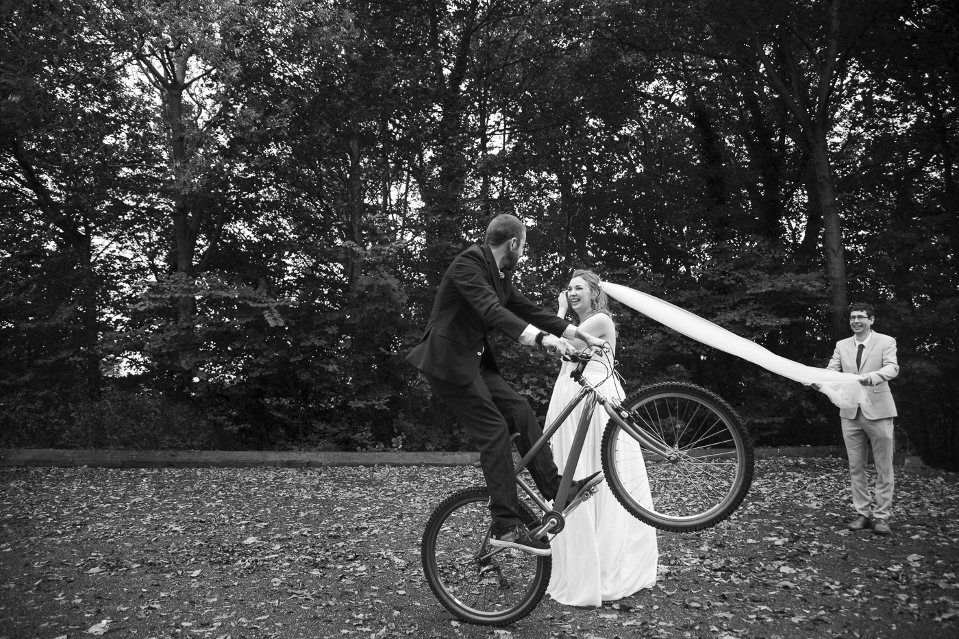 Groom on bike and bride with veil by Joshua Wyborn