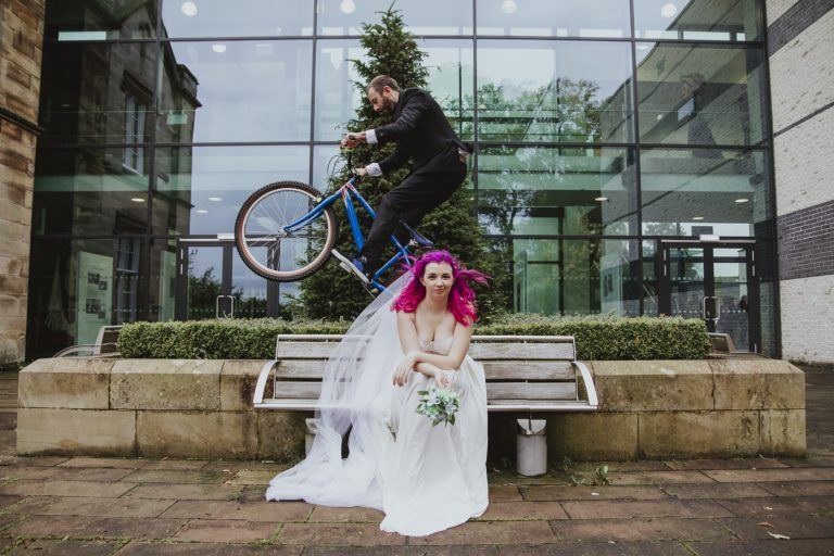 Bride with pink bride and groom cycling over bench by Joshua Wyborn
