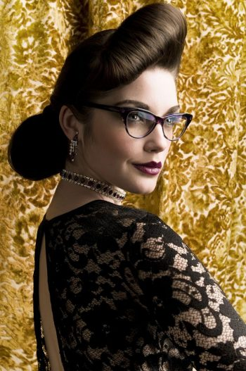 Woman in makeup in thick rimmed glasses, quiffed hair and black lace dress