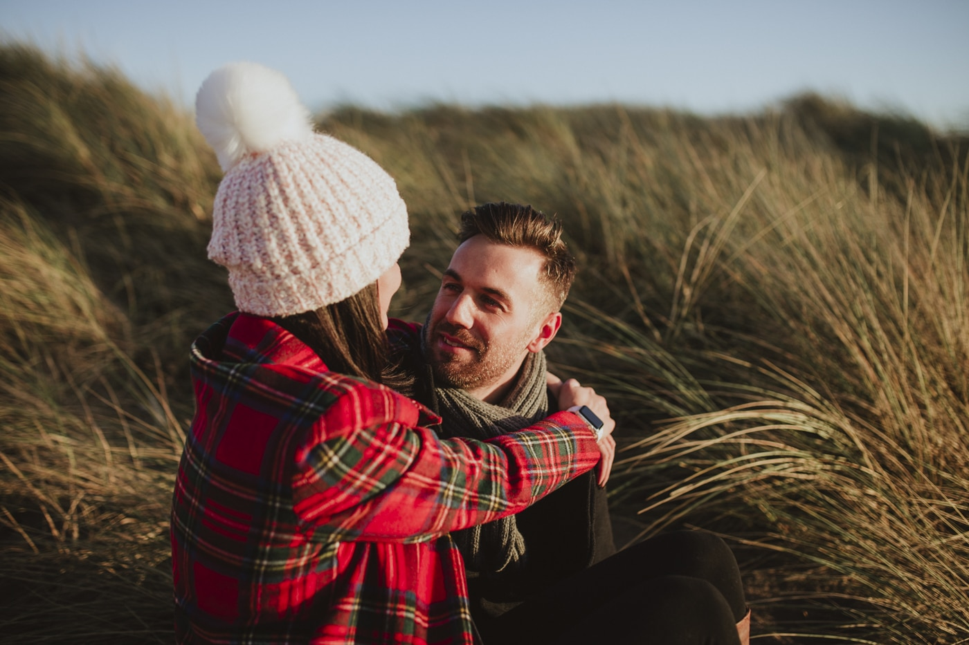 Cumbrian couple with tartan and bobble hat sitting in sand dunes by Joshua Wyborn