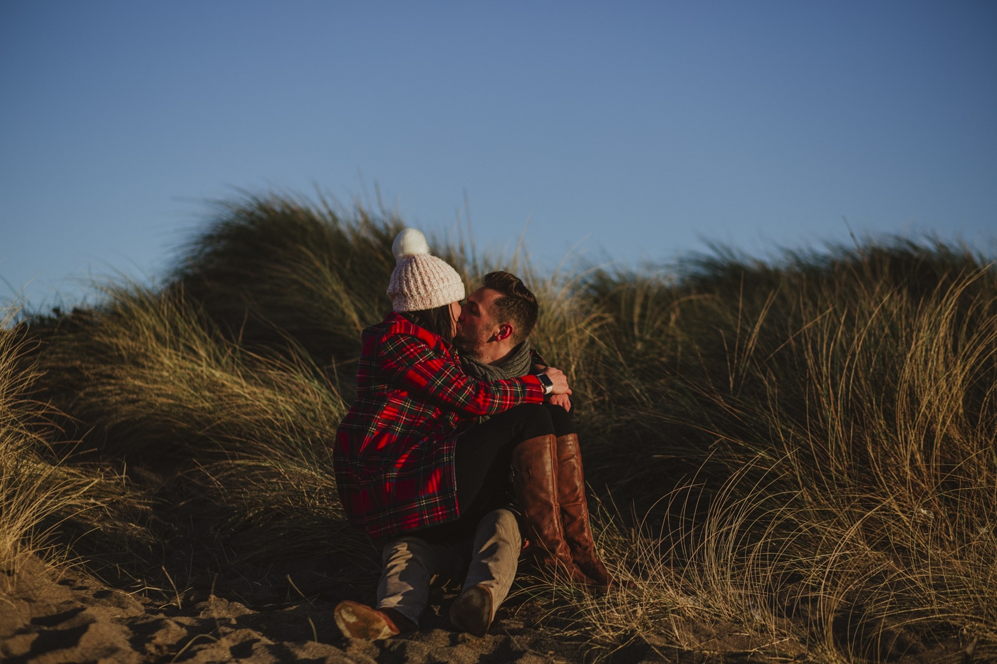 Man and woman sitting in the sand dunes kissing by Joshua Wyborn