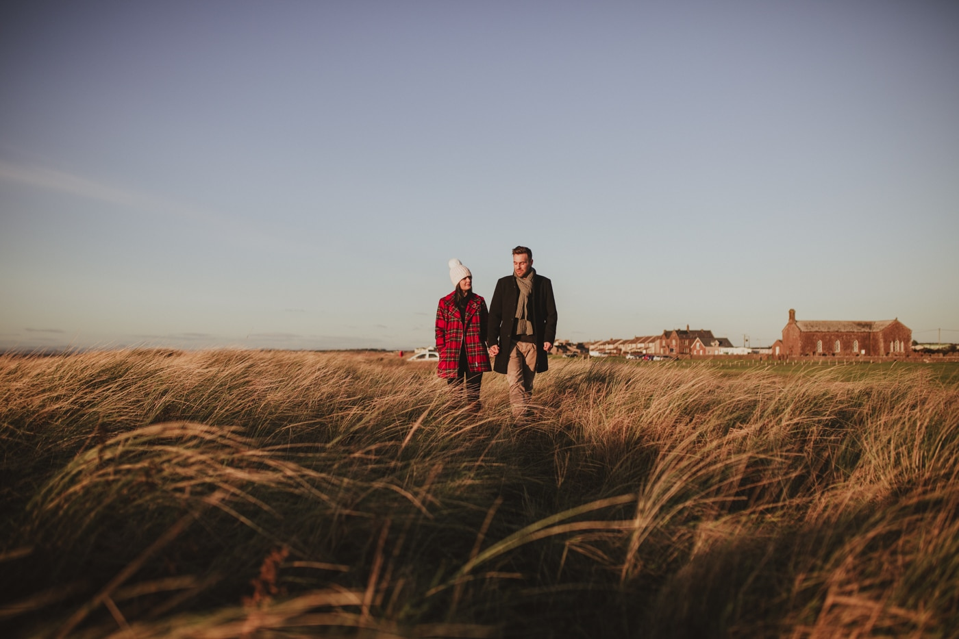 Couple holding hands walking along the tall grass in the blue skies by Joshua Wyborn