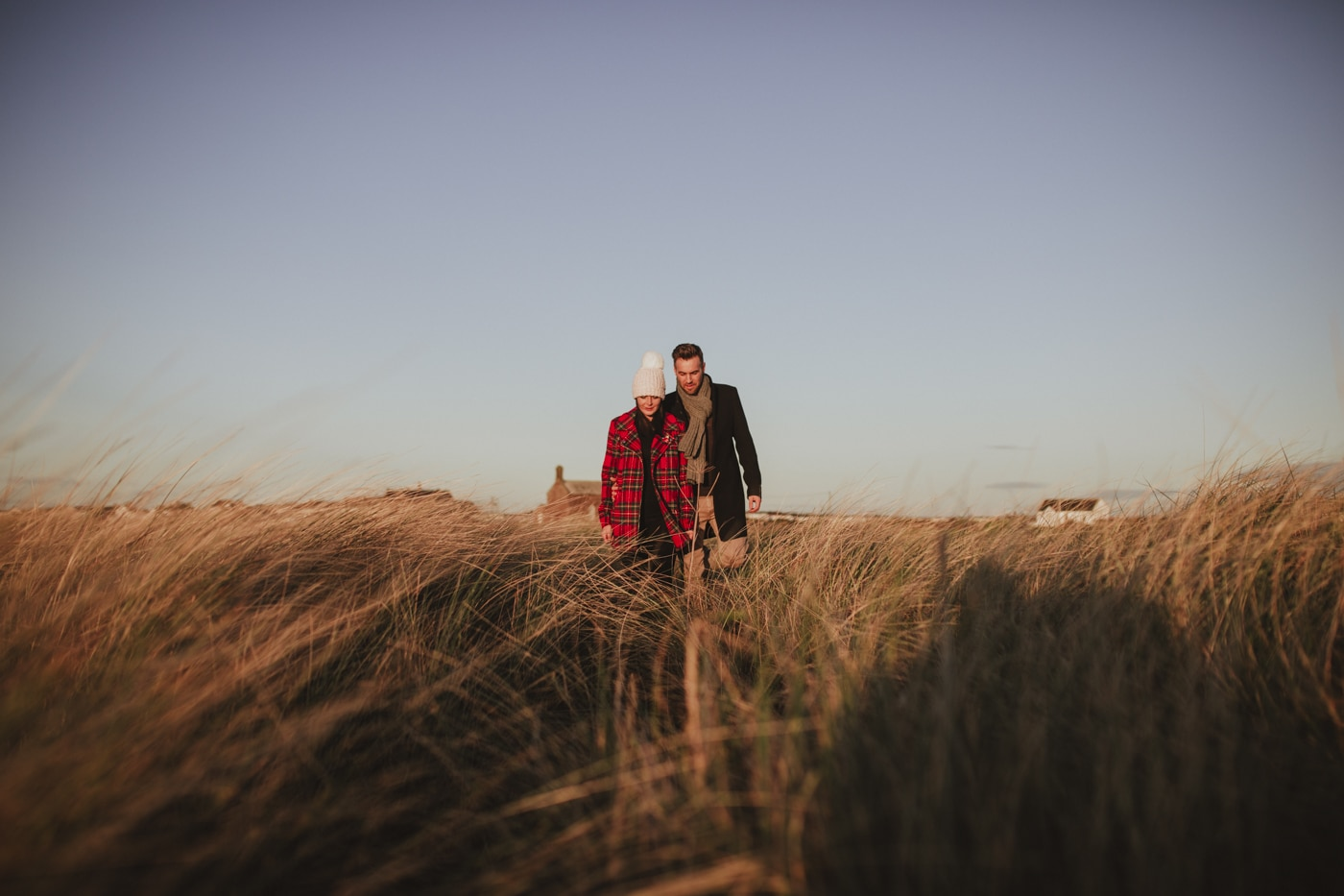 Man and woman in tartan coat and bobble hat walking in the sand dunes and tall grass