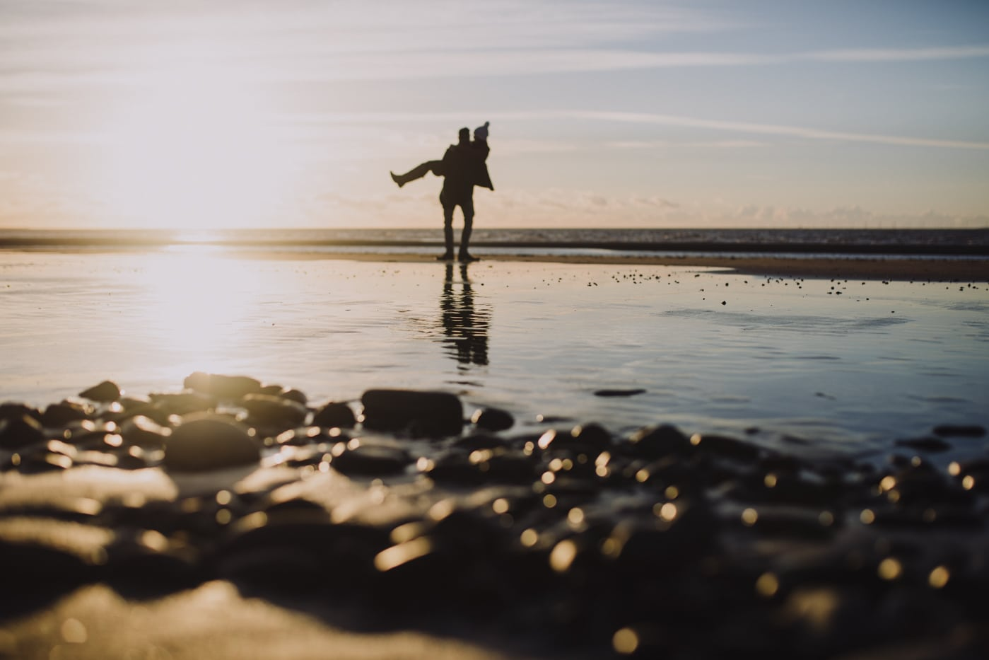 Man lifting woman on cumbrian coast portrait session by Joshua Wyborn Photographic