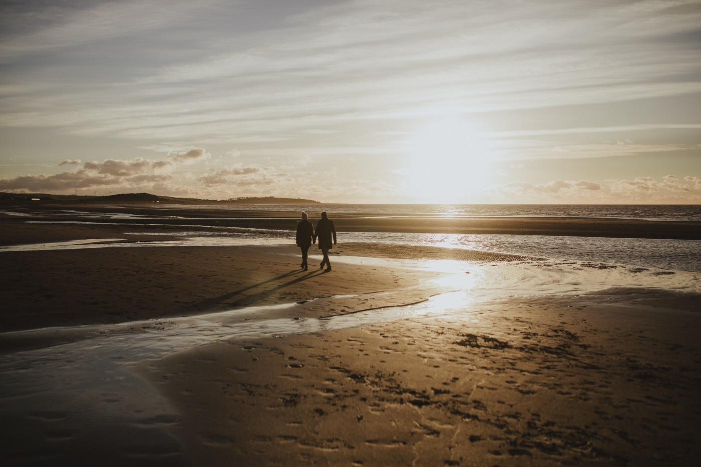 Couple walking on the Cumbrian beach in the sunset by Joshua Wyborn Photographic