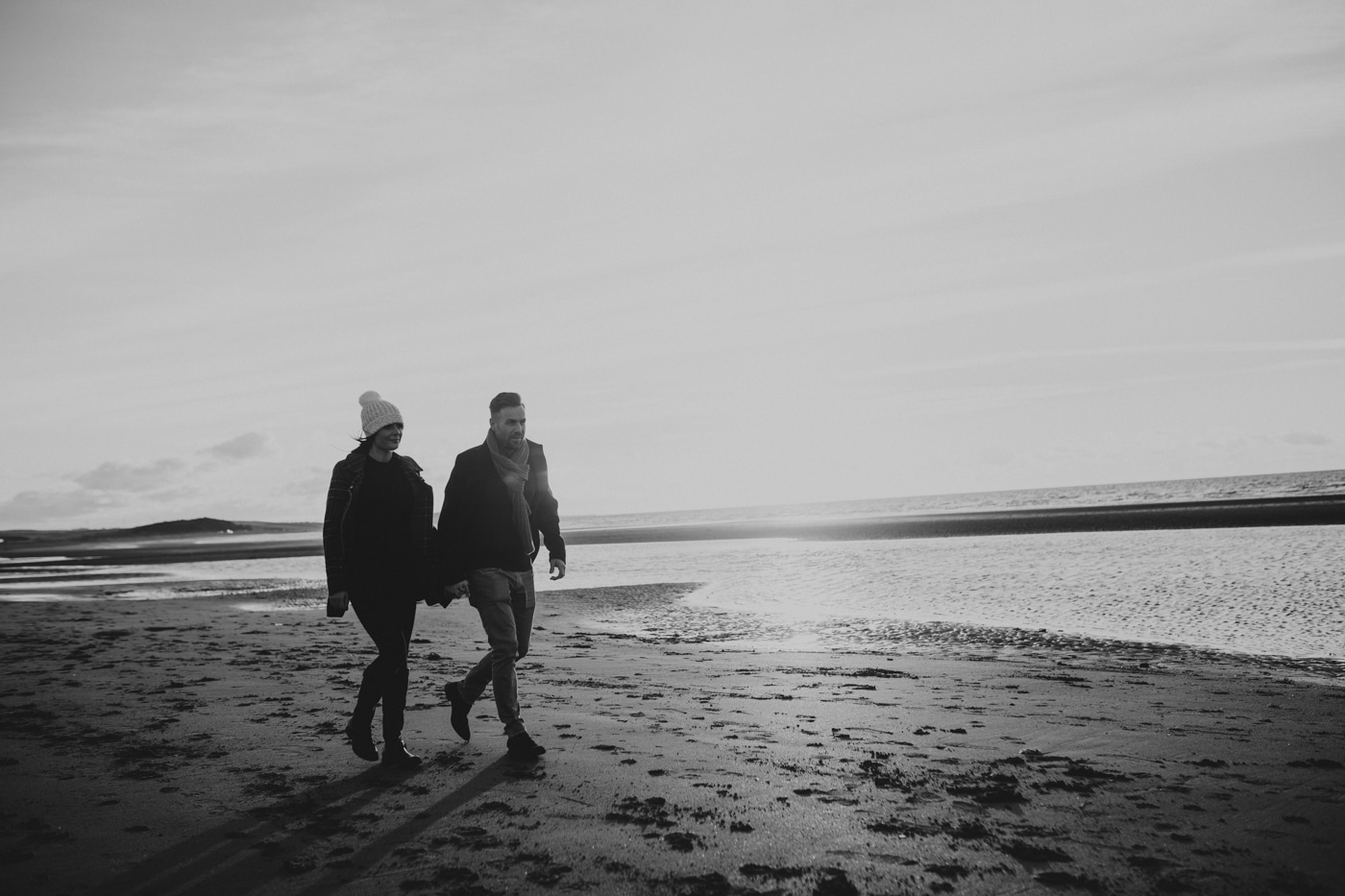 Man and woman in bobble hat walking along the beach by Joshua Wyborn Photographic