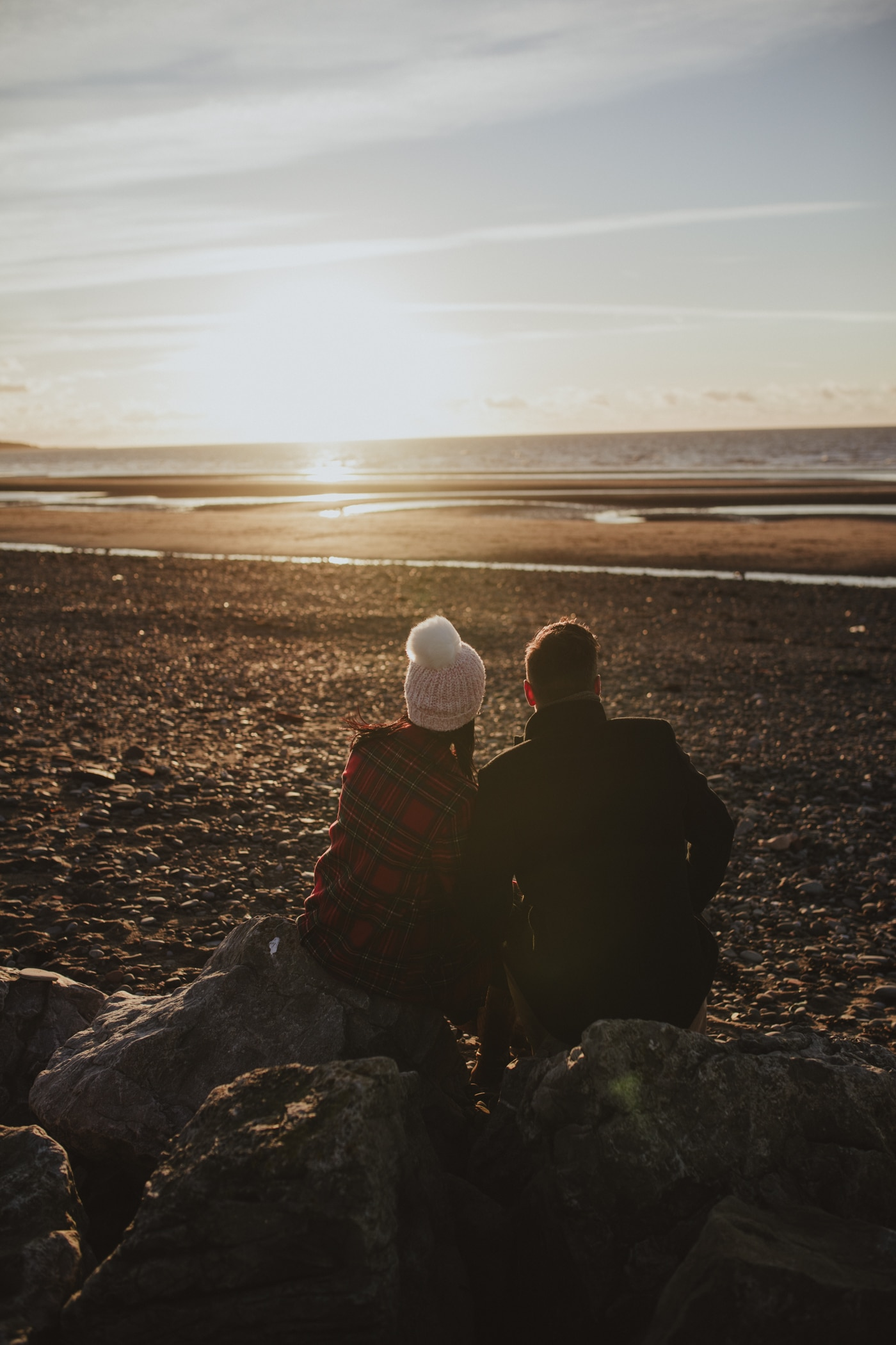 Man and woman in hat sitting on rock next to sea by Joshua Wyborn Photographic