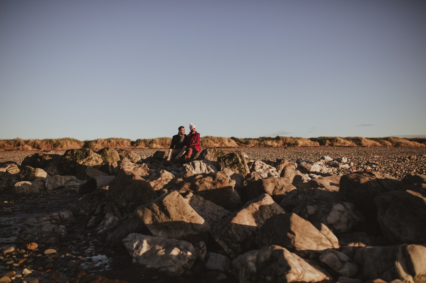 Man and woman on beach in cumbria looking out to the sea with blue skies by Joshua Wyborn Photographic