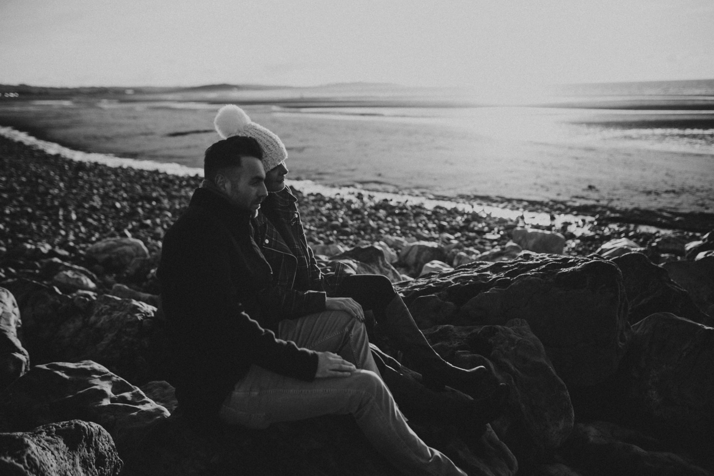 Man and woman on beach in cumbria by Joshua Wyborn