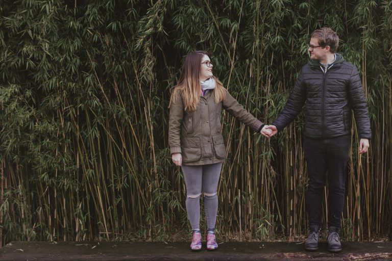 Man and woman in glasses and coats looking at each other in front of greenery by Joshua Wyborn Photographic