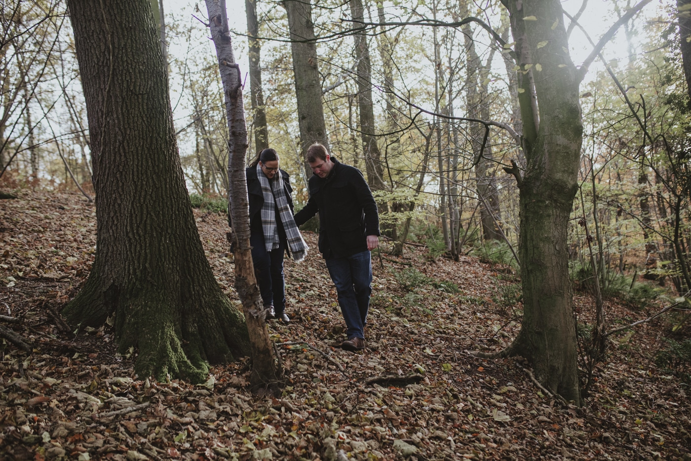 Man helping fiance down steep slope in leaves and woods by Joshua Wyborn Photographic