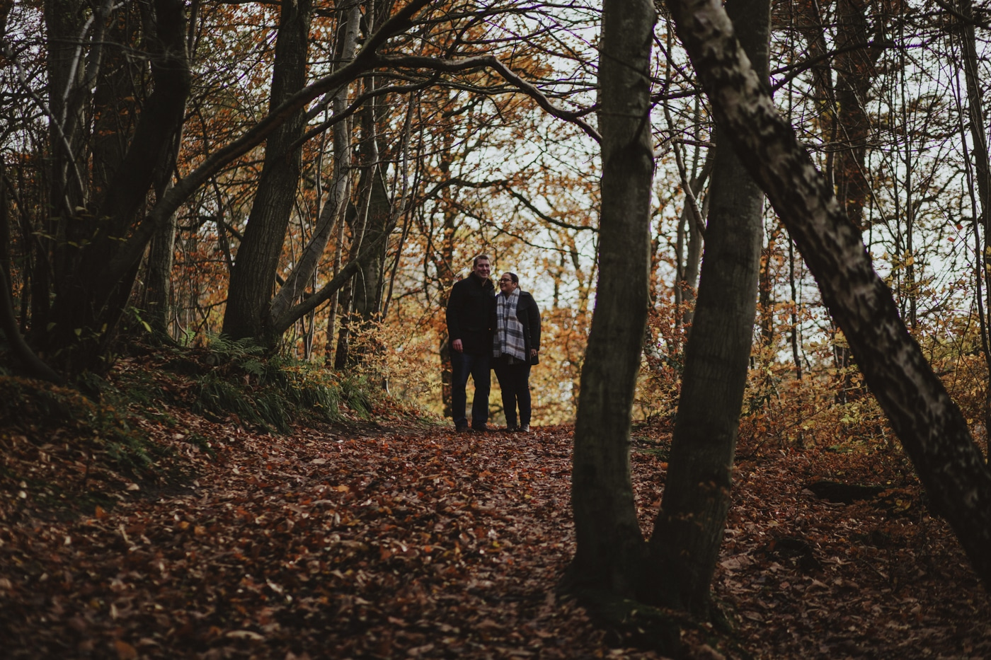 Man and woman standing in the light as it comes through the trees by Joshua Wyborn Photographic