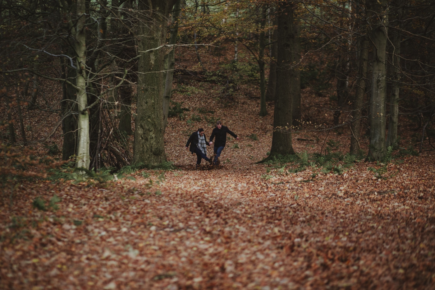 Man and woman kicking leaves at each other in the woodland by Joshua Wyborn Photographic