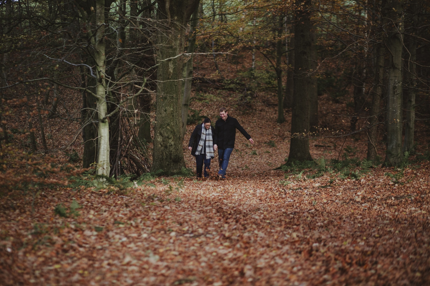 Man and woman walking up the hill in the leaves by Joshua Wyborn Photographic