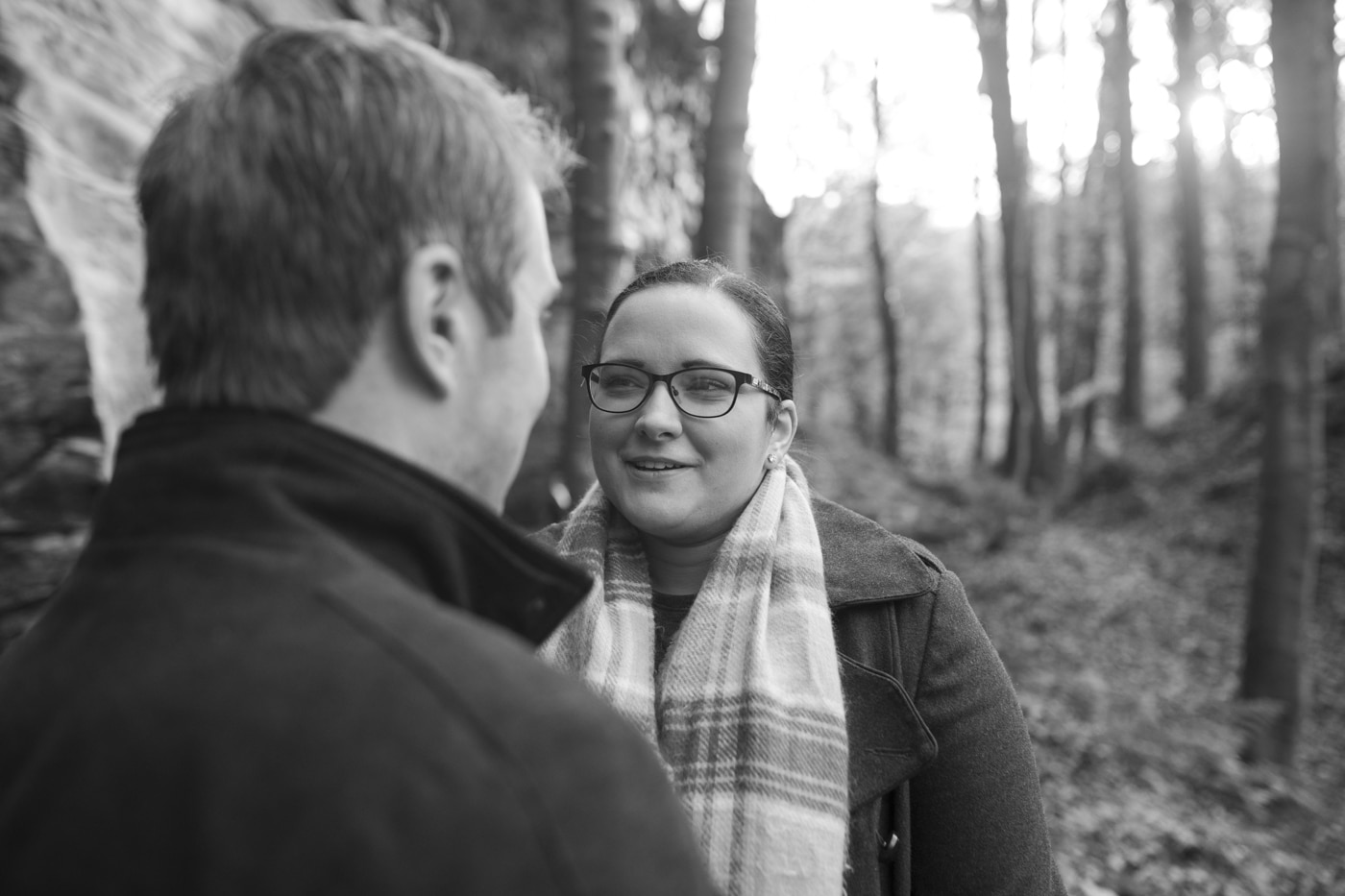 Man and woman in glasses and scarf looking at each other in woods by Joshua Wyborn