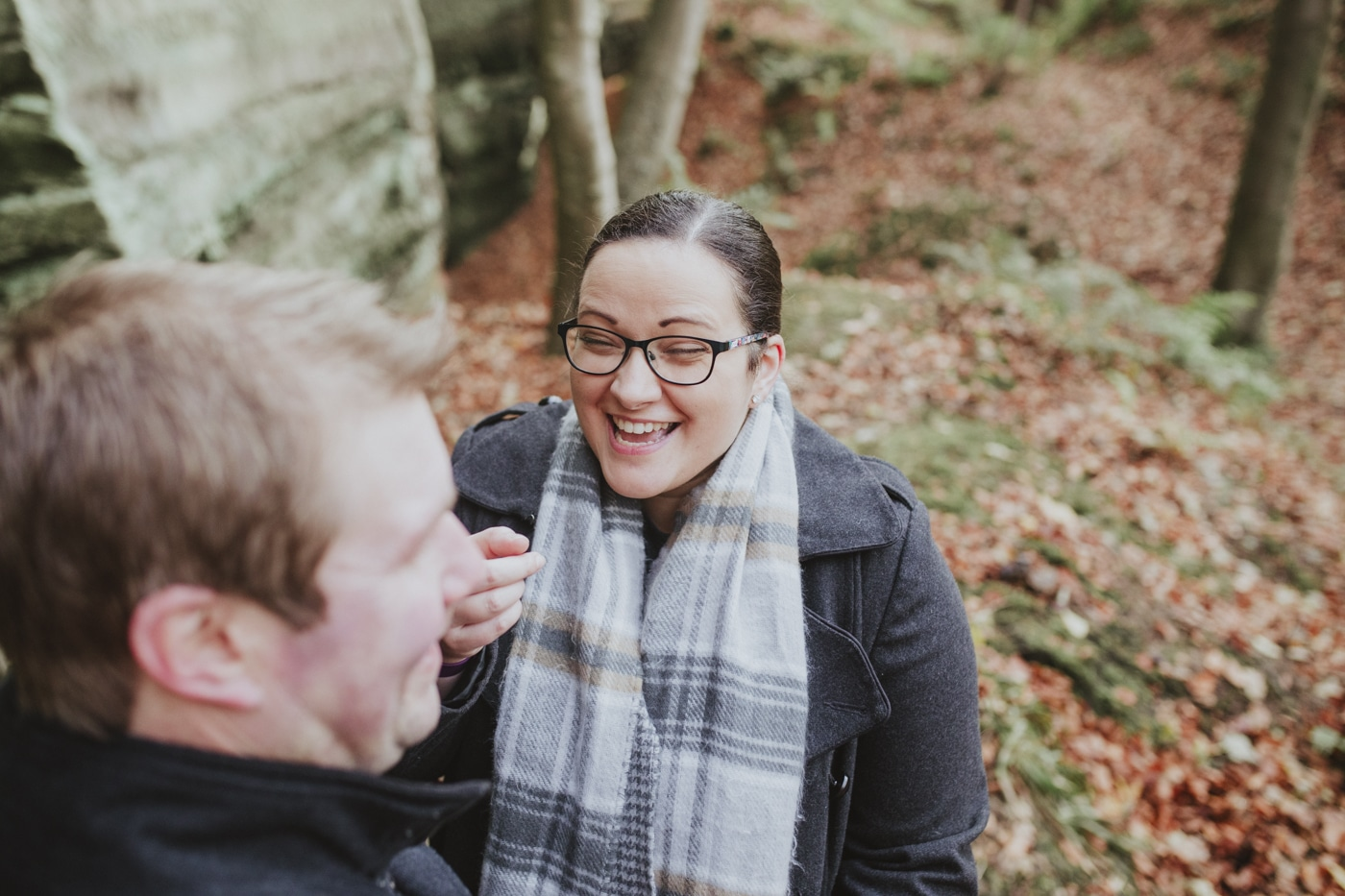Woman laughing at man in check scarf during portrait session