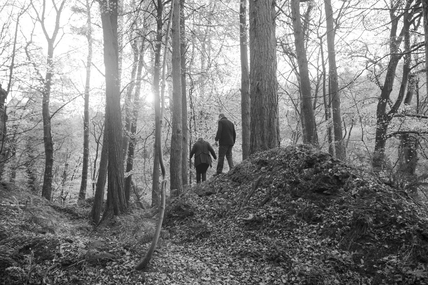 Man and woman walking through tall woods by Joshua Wyborn