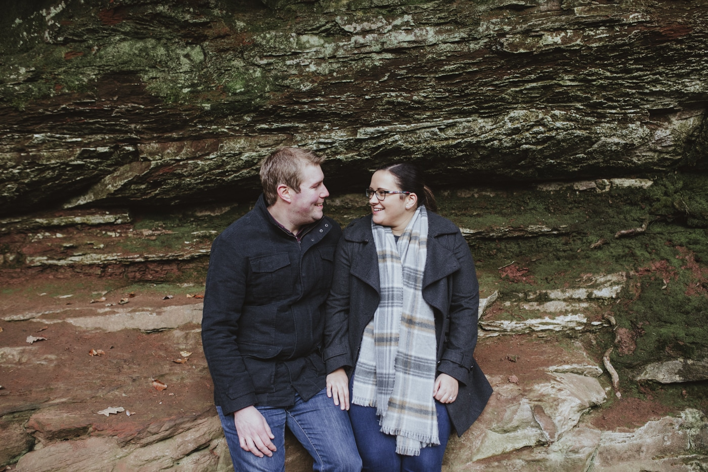 Couple sitting together on a rock during couple portrait shoot by Joshua Wyborn