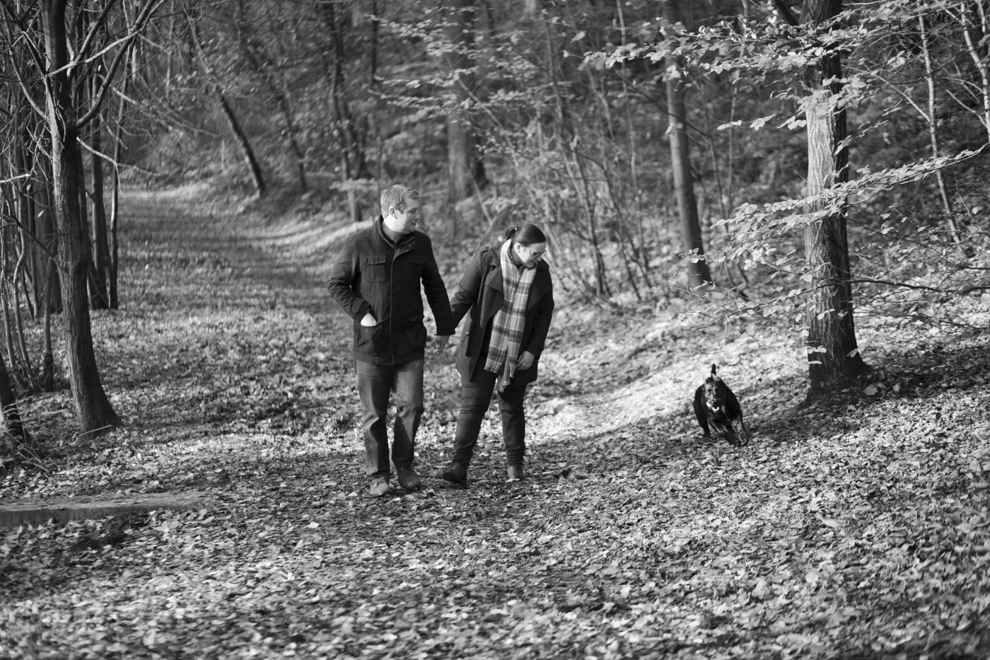 Man and woman with dog strolling through woods by Joshua Wyborn Photographic