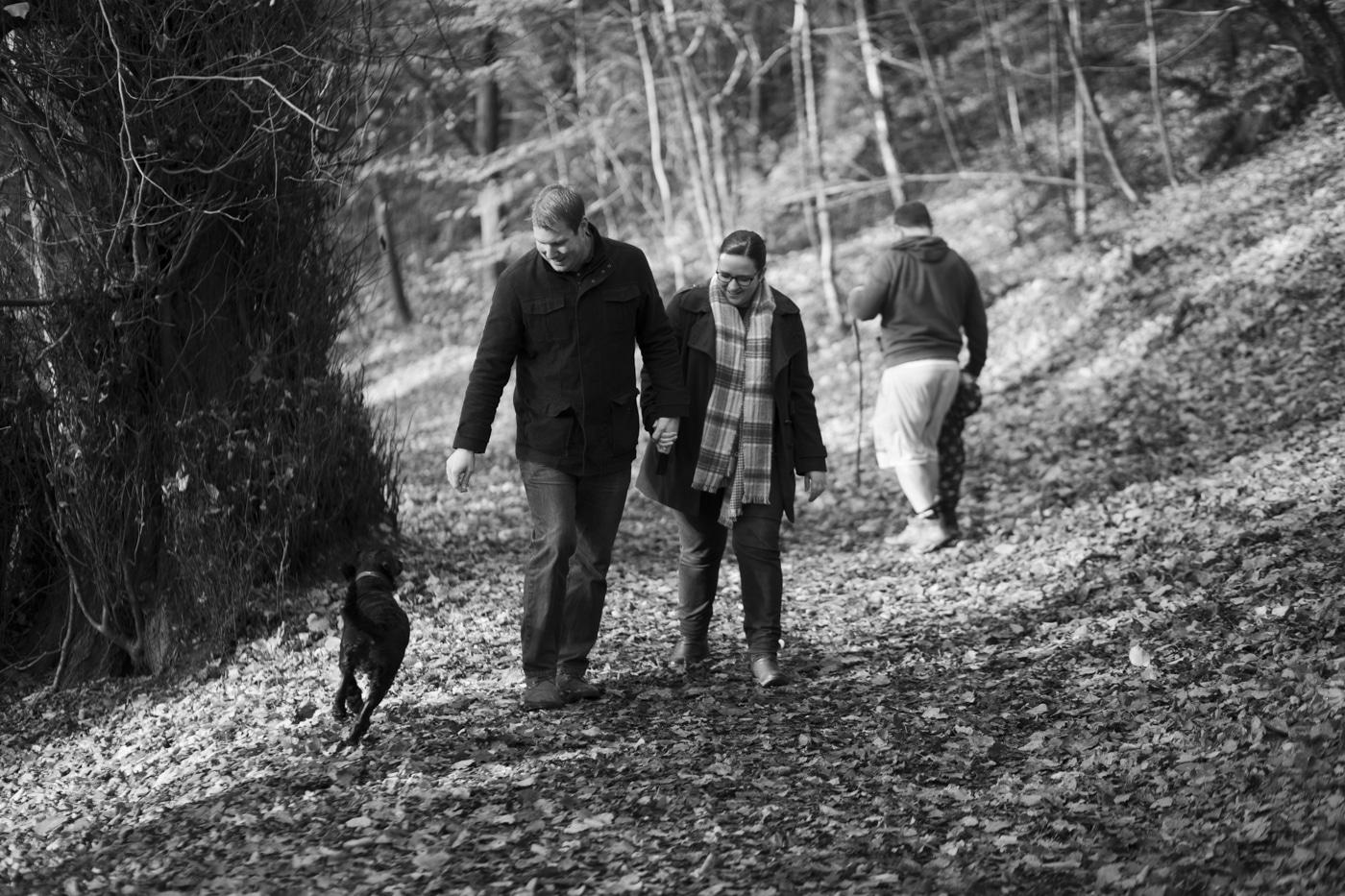Engaged couple watching dog run through woods by Joshua Wyborn Photographic