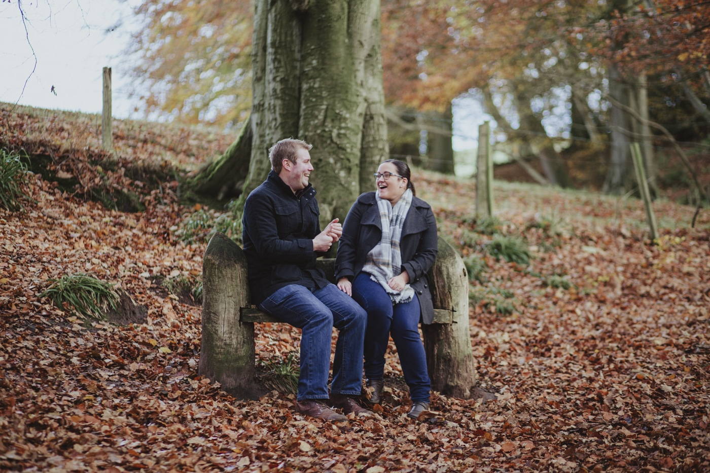 Engaged couple laughing and sitting on bench amongst leaves by Joshua Wyborn Photographic