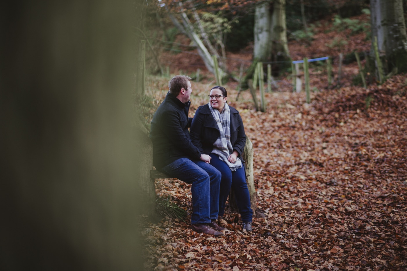 Engaged couple sitting on bench with leaves and trees surrounding them by Joshua Wyborn Photographic