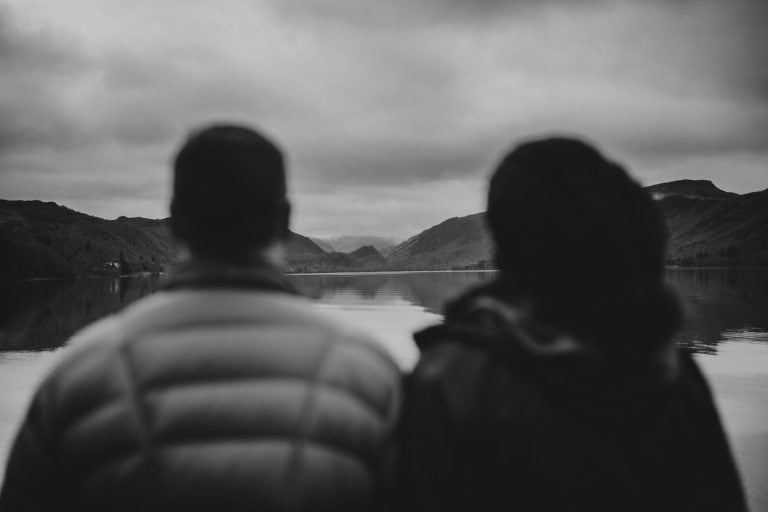 silhouette of man and woman in front of Cumbrian mountain and lake by Joshua Wyborn Photographic