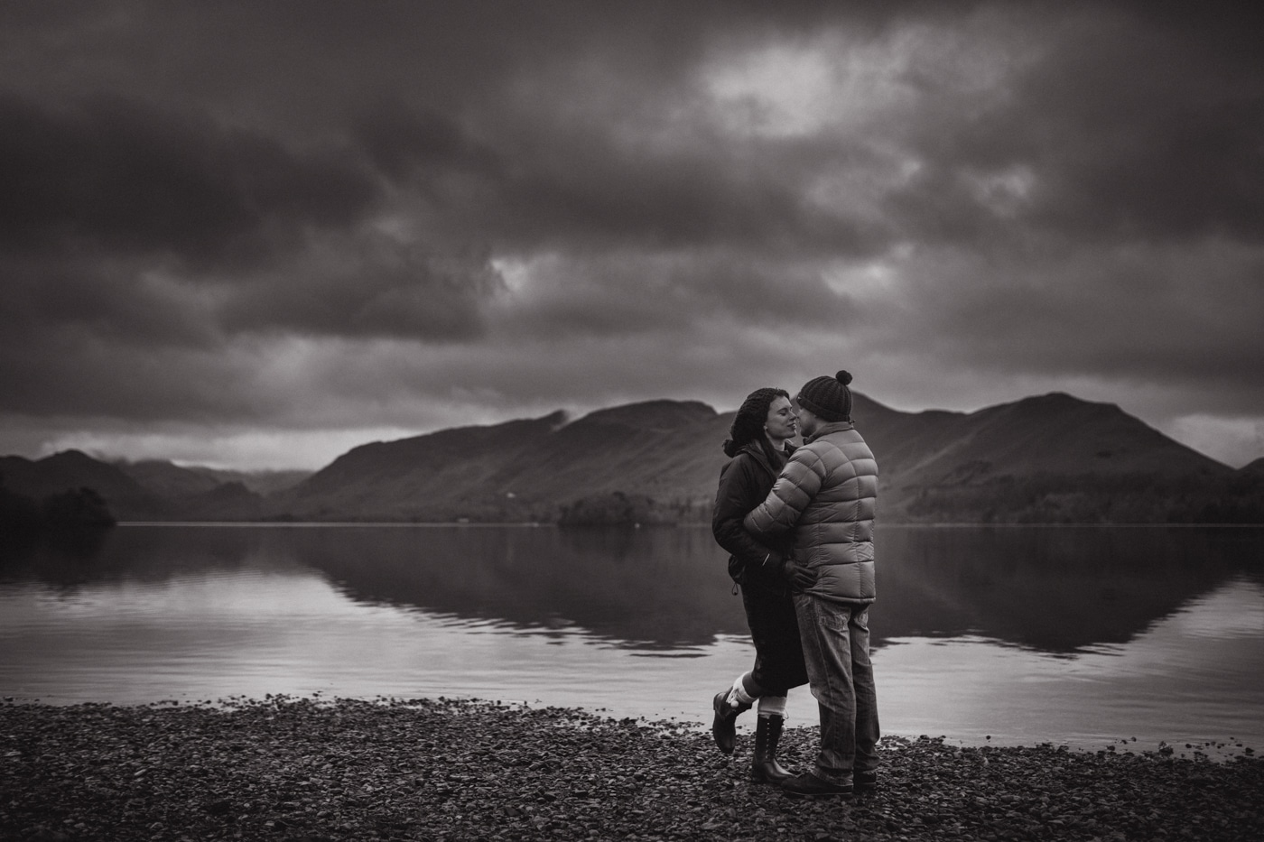 Couple embracing on shore of lake with mountains in the background by Joshua Wyborn Photography