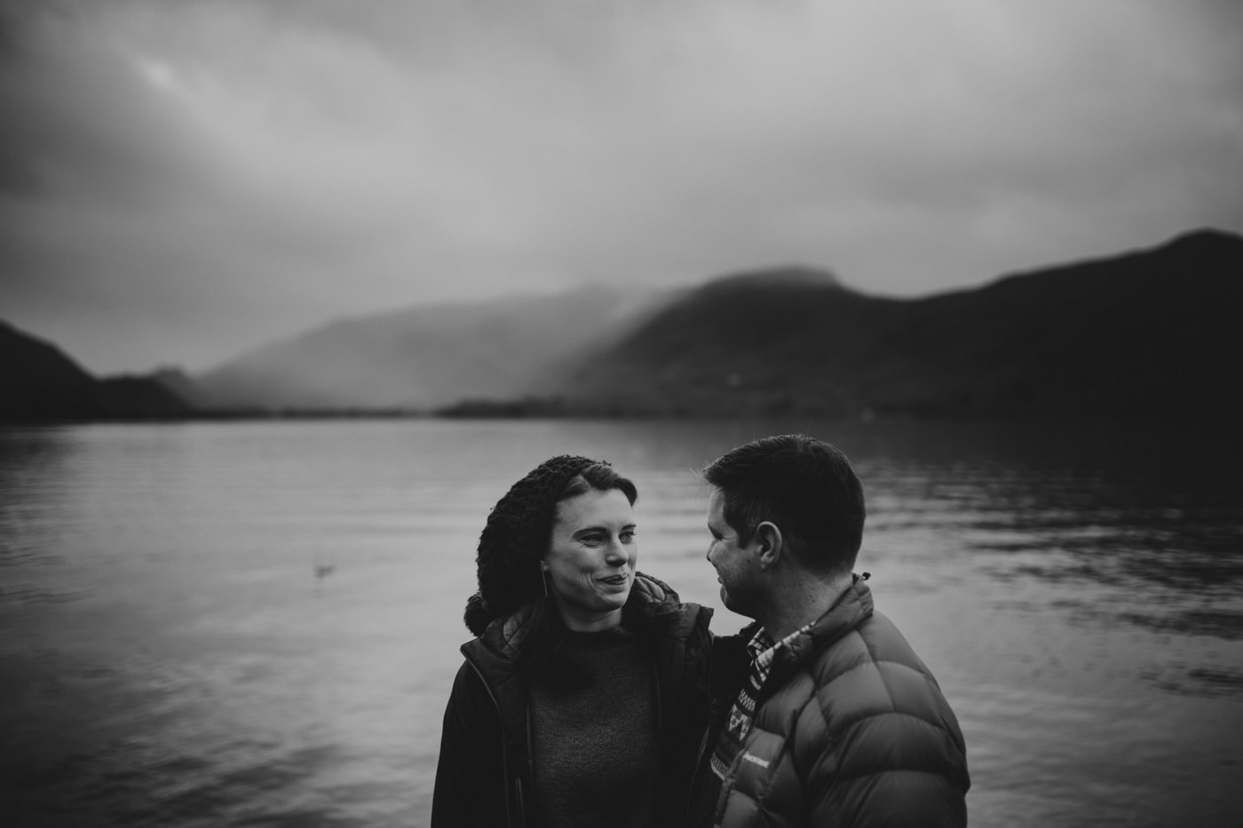 Man and woman in front of water and mountains Lake District and Cumbria Based Wedding Photographer Joshua Wyborn Photographic