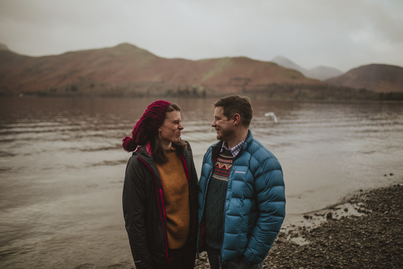 Man and woman making faces in front of lake and mountains in Cumbria