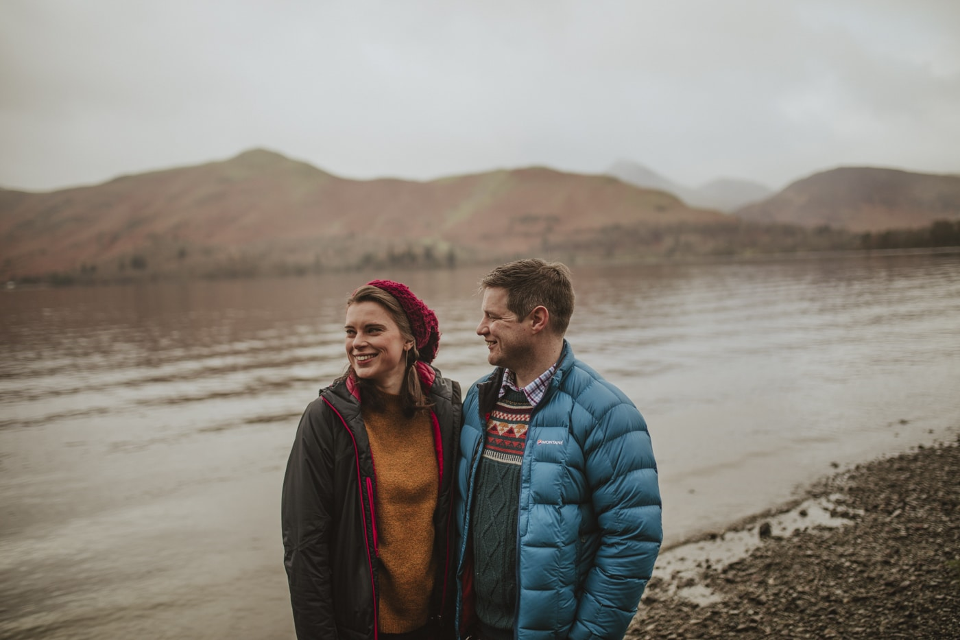 Couple stand by shore of lake and mountain in Cumbria by Joshua Wyborn Photographic