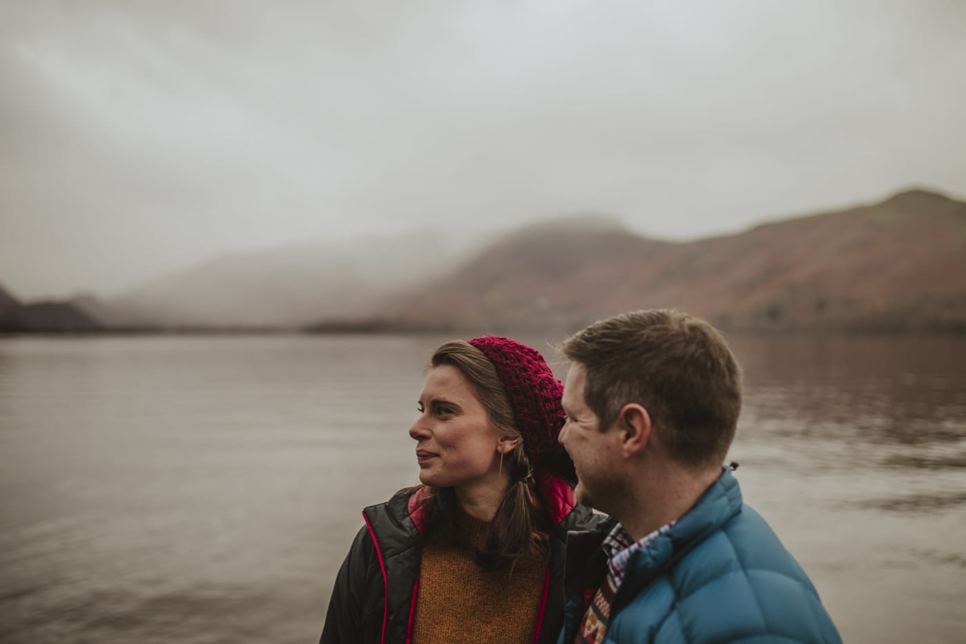 Couple looking out over lake and scenery in Cumbria by Joshua Wyborn
