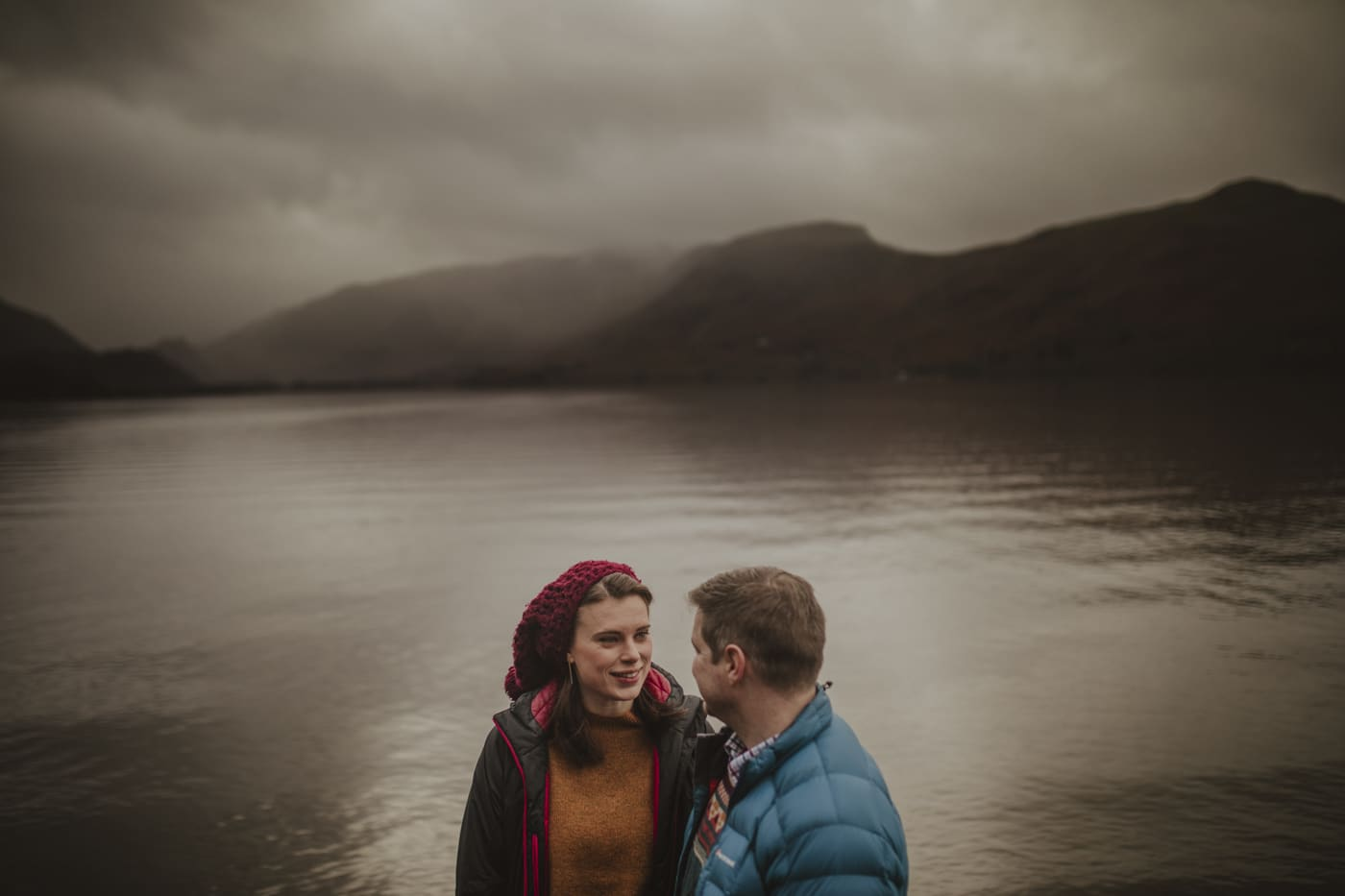 Man and woman standing in front of grey lake by Joshua Wyborn Photographic
