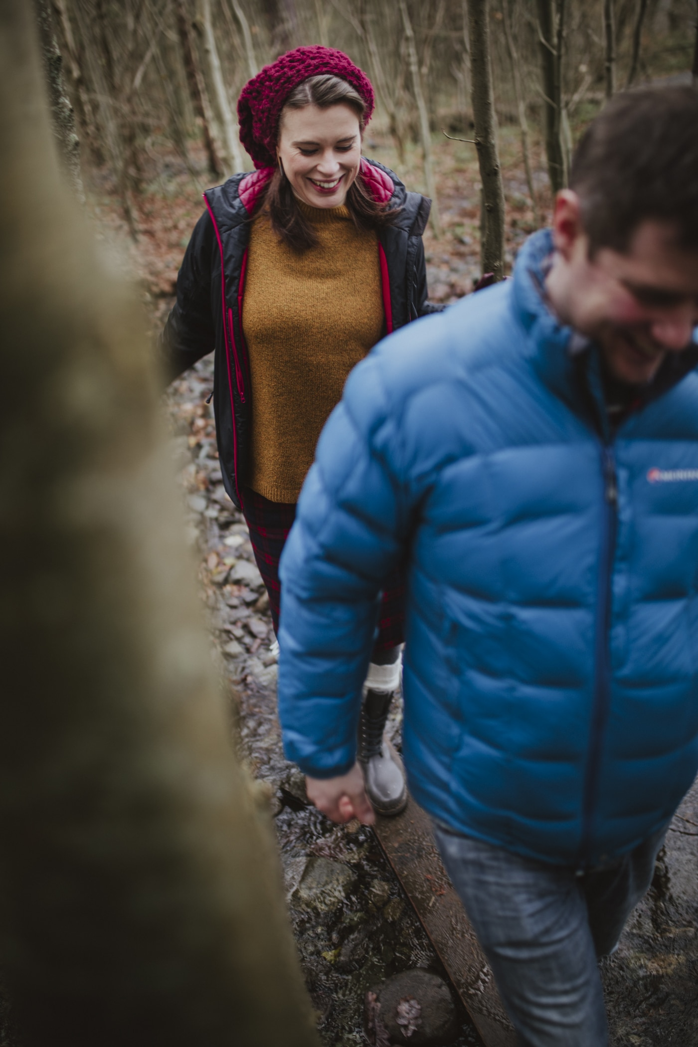 Happy Couple Portrait walking through the woods in Cumbria by Joshua Wyborn Photographic