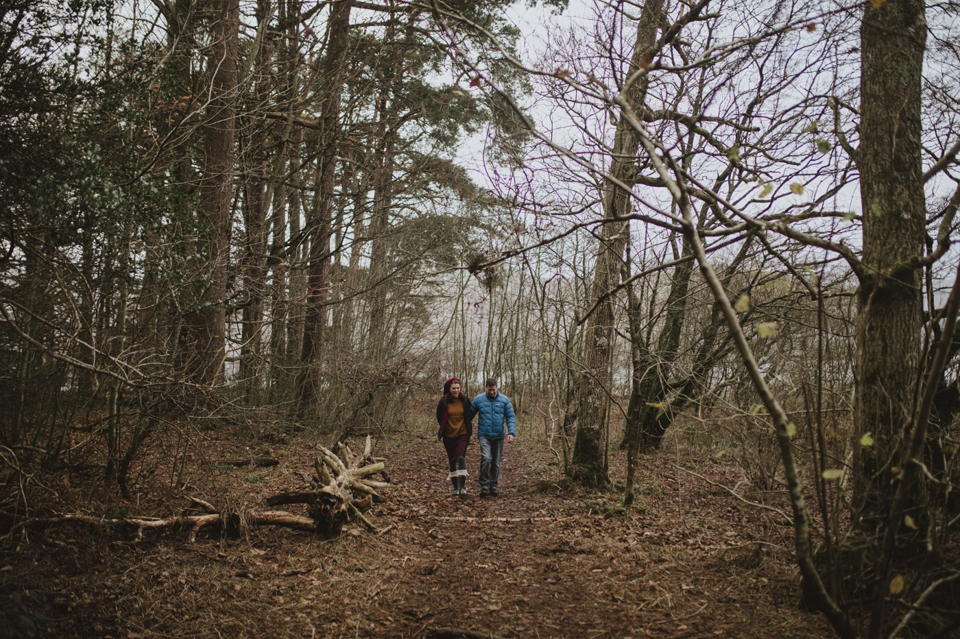 Couple portrait amongst tall trees in December weather by Joshua Wyborn
